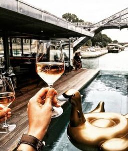 Holding wine in glass looking over the Seine